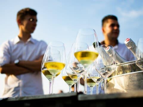 Weingläser und zwei Männer im Hintergrund